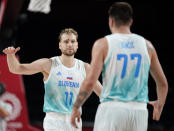 Slovenia's Jaka Blazic (11) celebrates with teammate Luka Doncic (77) during men's basketball quarterfinal game against Germany at the 2020 Summer Olympics, Tuesday, Aug. 3, 2021, in Saitama, Japan. (AP Photo/Charlie Neibergall)