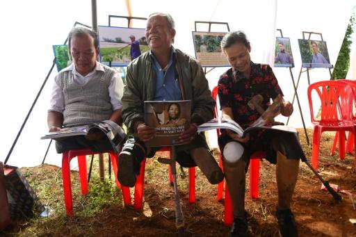 Vietnamese landmine victims (from left) Phan Van Ty, Truong Uu and Hoang Thi Luu read books in Quang Tri province in January 2020