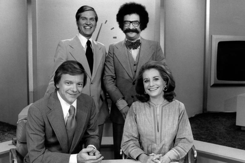 """This 1970s image released by NBC shows, clockwise from foreground left Jim Hartz, Lew Wood, Gene Shalit, and Barbara Walters from the NBC News """"Today"""" show in New York. Wood, a veteran broadcast journalist who covered the 1963 assassination of John F. Kennedy for CBS and later anchored the news report for NBC's """"Today"""" show, died Wednesday, Aug. 21, 2013 at a hospice in Riverside County, Calif. He was 84. (AP Photo/NBC)"""