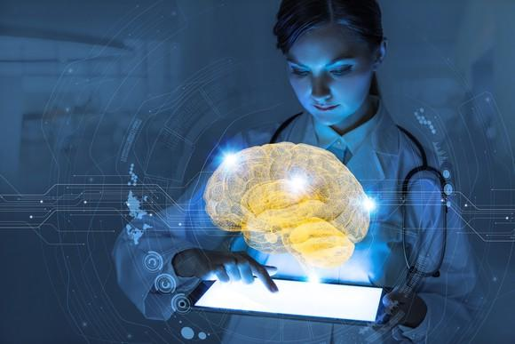 Female doctor holding tablet with digital image of brain displayed over tablet