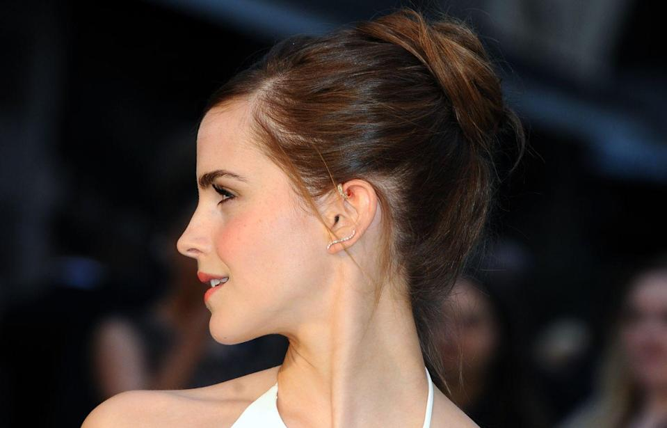 """<p>Emma flaunts her forward <a href=""""https://www.cosmopolitan.com/uk/fashion/style/a9538746/what-is-a-helix-piercing/"""" rel=""""nofollow noopener"""" target=""""_blank"""" data-ylk=""""slk:helix piercing"""" class=""""link rapid-noclick-resp"""">helix piercing</a> with a prominent gold hoop earring and keeps it simple on the bottom with a thin, curved diamond lobe earring. </p>"""