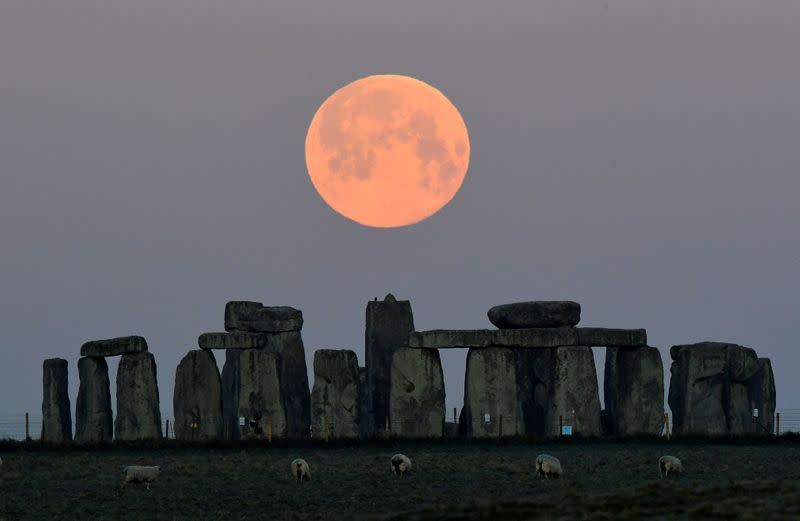 """FILE PHOTO: The full moon, known as the """"Super Pink Moon"""", sets behind Stonehenge stone circle near Amesbury"""