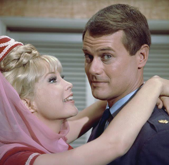 "Barbara Eden's Jeannie wraps her hands around Larry Hagman's Major Anthony Nelson, who freed her from her bottle in the 1960s sitcom, ""I Dream of Jeannie."""