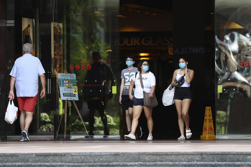 """People wearing protective face masks exit a mall along the Orchard Road shopping belt in Singapore, Friday, April 10, 2020. The Singapore government put in place """"circuit breaker"""" measures in the light of a sharp increase of COVID-19 cases in recent days. Under the measures which will last through May 4, people have to stay home and step out only for essential tasks, such as going to work if they are in essential services, buying food and groceries, or for a short bout of exercise. (AP Photo/Yong Teck Lim)"""