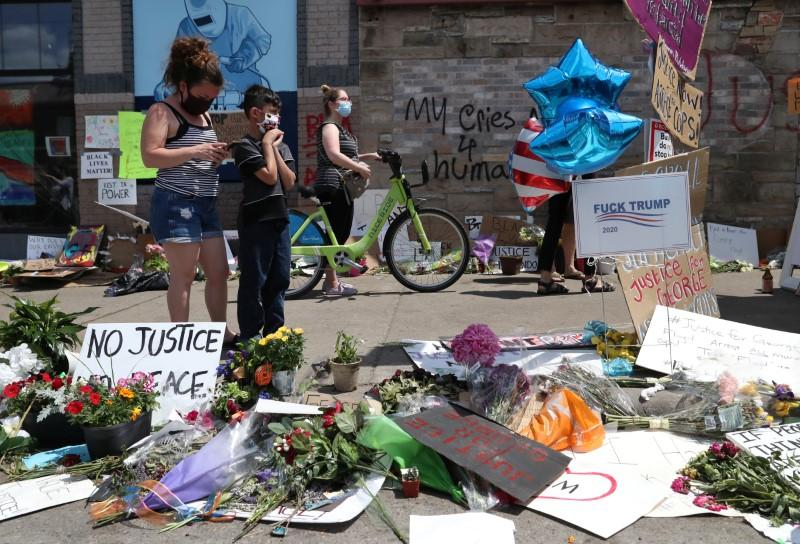 People gather at a memorial for George Floyd at the place where he was taken into police custody and later died in Minneapolis