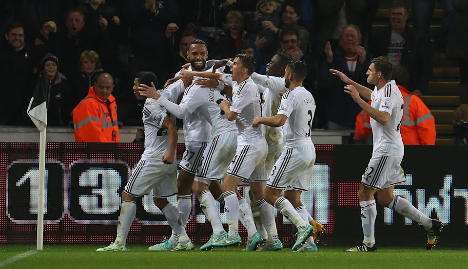 Swansea players celebrate after Swansea City's Icelandic midfielder Gylfi Sigurdsson (3L) scored an equalising goal against Arsenal in Swansea, south Wales on November 9, 2014 (AFP Photo/Geoff Caddick)