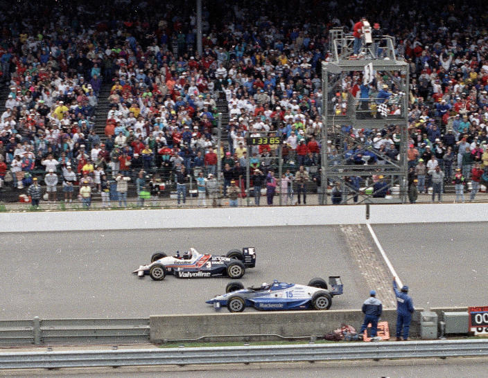 FILE - In this May 24, 1992, file photo, Al Unser Jr., top, wins the Indianapolis 500 auto race by less than a car length ahead of Scott Goodyear in the 76th running of the race at Indianapolis Motor Speedway in Indianapolis. The Associated Press has updated its survey of living Indianapolis 500 winners and their pick as the greatest race in the long history of the event. There are six races that received multiple votes, topped by Unser victory over Goodyear in 1992 — the closest Indy 500 in history. The others are Emerson Fittipaldi's win in 1989; Sam Hornish Junior's win in 2006; the 1982 battle between Rick Mears and Gordon Johncock; the 2011 race won by the late Dan Wheldon; and the 2014 thriller won by Ryan Hunter-Reay. (AP Photo/David Boe, File)