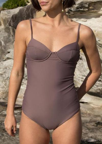 A photo of a model wearing Baythe's balconette one-piece swimsuit in cocoa.
