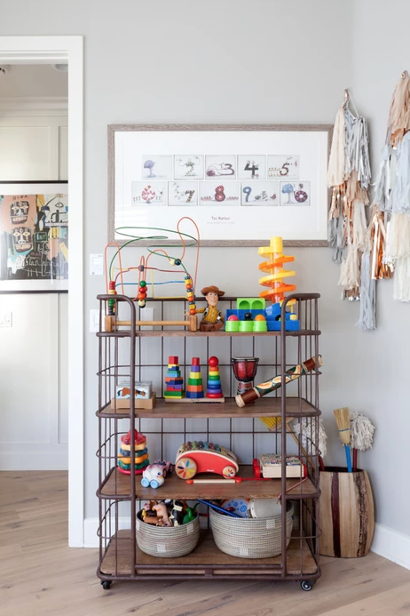 """<p>Who says toy storage can't be chic? This vintage-style shelving rack makes a colorful bead maze look like a sculpture on display.</p><p><strong>See more at </strong><strong><a href=""""https://www.veneerdesigns.com/playa-vista-i"""" rel=""""nofollow noopener"""" target=""""_blank"""" data-ylk=""""slk:Veneer Designs"""" class=""""link rapid-noclick-resp"""">Veneer Designs</a>.</strong></p><p><strong><a class=""""link rapid-noclick-resp"""" href=""""https://go.redirectingat.com?id=74968X1596630&url=https%3A%2F%2Fwww.wayfair.com%2Ffurniture%2Fpdp%2Fgracie-oaks-azariah-4-tier-bar-cart-w001562344.html&sref=https%3A%2F%2Fwww.redbookmag.com%2Fhome%2Fg36014277%2Ftoy-organizer-ideas%2F"""" rel=""""nofollow noopener"""" target=""""_blank"""" data-ylk=""""slk:SHOP STORAGE CART"""">SHOP STORAGE CART</a><br></strong></p>"""
