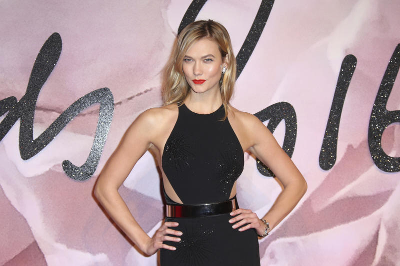"""FILE - This Dec. 5, 2016 file photo Model Karlie Kloss poses for photographers at the Fashion Awards in London. Kloss is apologizing for appearing in a fashion spread in Vogue's diversity issue styled as a geisha. The model, who has Danish and German roots, was photographed by Mikael Jansson in a black wig and wears a kimono in one shot and poses beside a sumo wrestler in another. In its introduction, Vogue writes that the spread is """"paying homage to geisha culture."""" (Photo by Joel Ryan/Invision/AP, File)"""