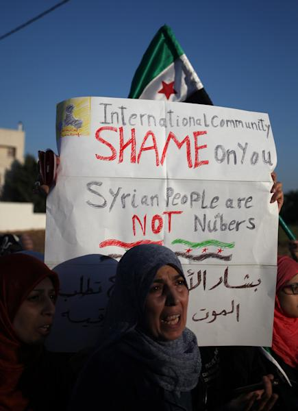 Syrian woman chants anti- President Assad slogans, during a protest in front of the Syrian embassy to condemn the alleged poison gas attack on the suburbs of Damascus, during a protest in front of the Syrian embassy, in Amman, Jordan, Friday, Aug. 23, 2013. Anti-government activists accused the Syrian regime of carrying out a toxic gas attack that is thought to have killed at least 100 people, including many children as they slept, during intense artillery and rocket barrages Wednesday on the eastern suburbs of Damascus that are part of a fierce government offensive in the area.(AP Photo/Mohammad Hannon)