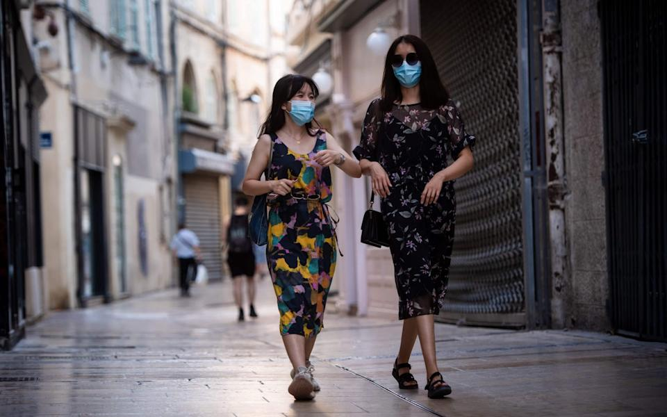 Women wearing face masks walk along a street in Avignon southern France - CLEMENT MAHOUDEAU/AFP