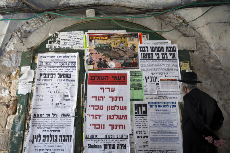 "In this Sunday, July 14, 2013 photo, an ultra-Orthodox Jewish man looks at posters in the ultra-Orthodox Jewish Mea Shearim neighborhood in Jerusalem. A large cartoon poster depicts Haredi soldiers rolling through the streets atop tanks trying to lure young boys onto their vehicles. The ad denounces the soldiers as Zionist ""ambassadors"" and ""missionaries."" The soldiers in sidecurls have been coined the insulting nickname ""Hardak"" _ a combination of Haredi and insect. (AP Photo/Sebastian Scheiner)"