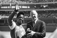 FILE - Atlanta Braves' Hank Aaron waves to the crowd as baseball commissioner Bowie Kuhn presents him with a trophy in Cincinnati after Aaron tied Babe Ruth's all-time home run mark, in this April 4, 1974, file photo. Aaron died Jan. 22, 2021. Kuhn was commissioner from Feb. 4, 1969 to Sept. 30, 1984. (AP Photo/Bob Johnson, File)