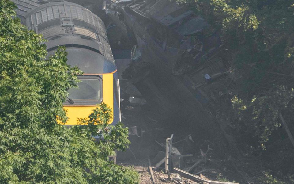 Derailed carriages are seen at the scene of a train crash near Stonehaven in northeast Scotland on August 12, 2020