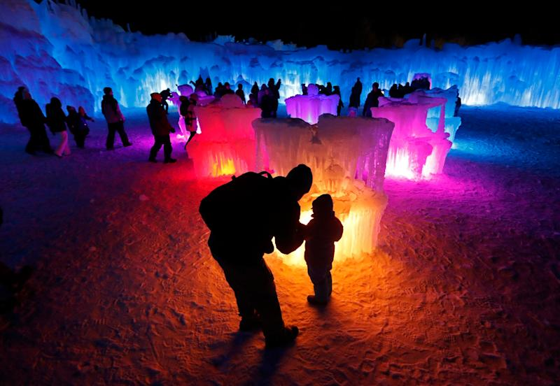 Bruce McCafferty and his son, Dougie, pause while exploring the ice formations growing at Ice Castles in North Woodstock, N.H. (Photo: Robert F. Bukaty/AP)