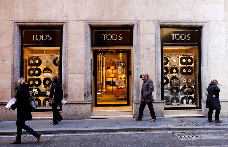 FILE PHOTO: People walk past a Tod's shop in downtown Rome