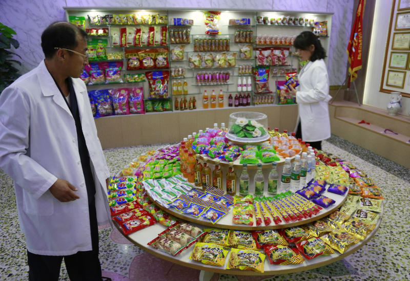 In this Oct. 22, 2018, photo, Kwon Yong Chol, left, the chief engineer at the Songdowon General Foodstuffs Factory, shows samples of products at his facility in Wonsan, North Korea. Though the international spotlight has been on his denuclearization talks with Washington, the North Korean leader has a lot riding domestically on his promises to boost the country's economy and standard of living. His announcement in April that North Korea had sufficiently developed its nuclear weapons and would now focus on building its economy marked a sharp turn in official policy and set the stage for his rapid-fire meetings with the leaders of China, South Korea and the United States. (AP Photo/Dita Alangkara)