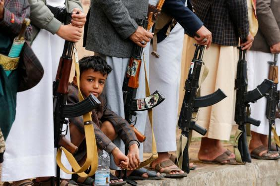 A boy sits among Houthi followers during a Houthi gathering in Sanaa (REUTERS)