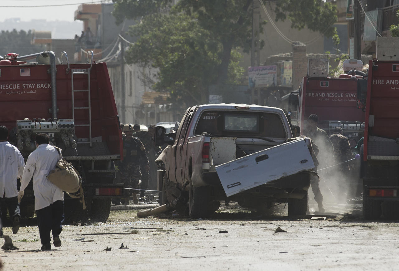 Afghan and U.S. soldiers arrive to the scene where a suicide car bomber attacked a NATO convoy in Kabul, Afghanistan, Thursday, May 16, 2013. A Muslim militant group, Hizb-e-Islami, claimed responsibility for the early morning attack, killing at least six people in the explosion and wounding more than 30, police and hospital officials said. The powerful explosion rattled buildings on the other side of Kabul and sent a pillar of white smoke into the sky in the city's east. (AP Photo/Anja Niedringhaus)