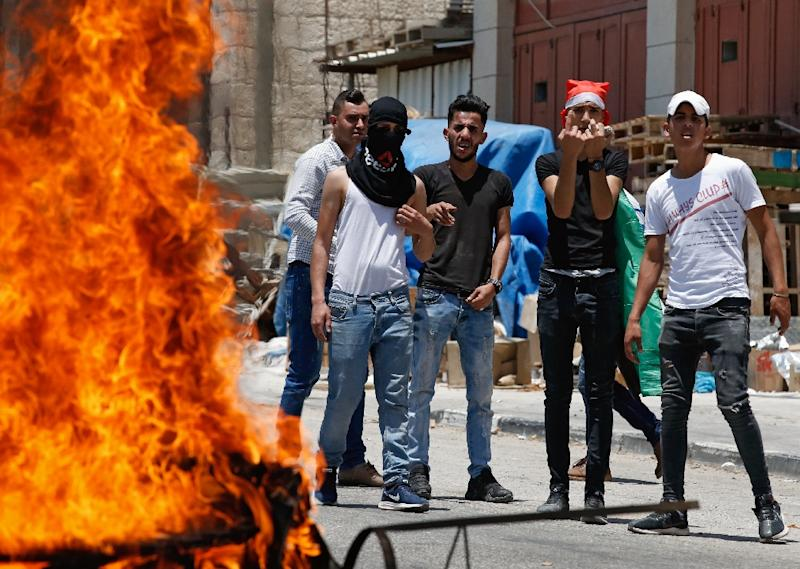 Stone-carrying Palestinians near Hebron stand behind a burning tyre as they protest against a US-led Middle East conference in Bahrain