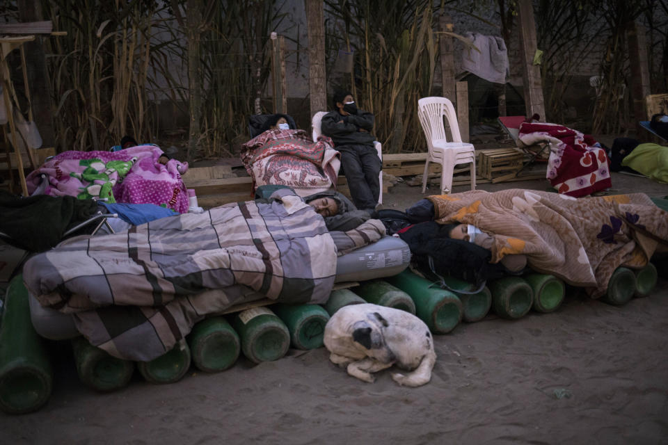People sleep on top of empty oxygen cylinders, waiting for a shop to open in order to refill their tanks, in the Villa El Salvador neighborhood, as a shortage of medical oxygen to treat COVID-19 patients continues in Lima, Peru, Tuesday, April 6, 2021. (AP Photo/Rodrigo Abd)