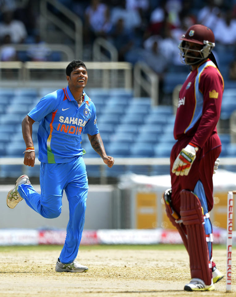 Indian cricketer Umesh Yadav (L) celebrates dismissing West Indies cricketer Chris Gayle (R) during the second match of the Tri-Nation series between Indian and West Indies at the Sabina Park stadium in Kingston on June 30, 2013. India have scored 229/7 at the end of their innings.   AFP PHOTO/Jewel Samad
