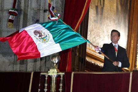 """FILE PHOTO: Mexico's President Enrique Pena Nieto waves the national flag after he shouted the """"Cry of Independence"""", as Mexico marks the 207th anniversary of the day rebel priest Miguel Hidalgo set it on the path to independence, in Mexico City, Mexico, September 15, 2017. REUTERS/Edgard Garrido"""