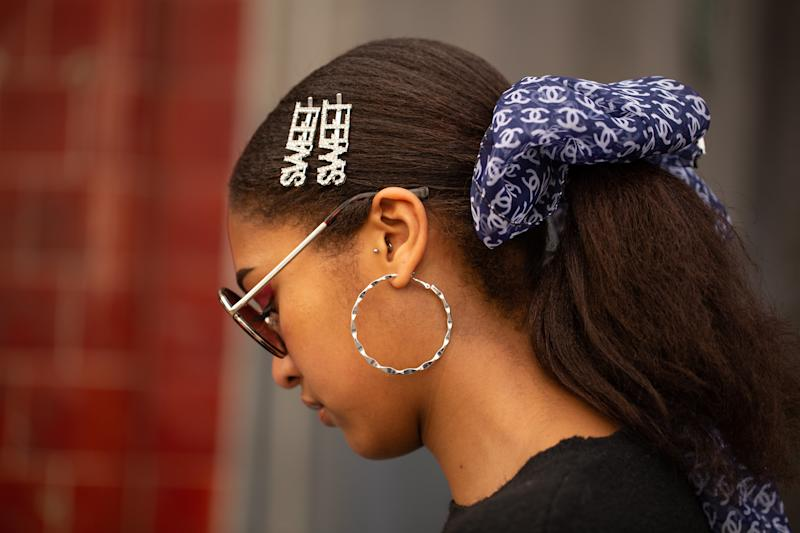 LONDON, ENGLAND - FEBRUARY 19: A guest is seen on the street during London Fashion Week February 2019 wearing navy Chanel hair bow with two 'Sweet' barrettes on February 19, 2019 in London, England. (Photo by Matthew Sperzel/Getty Images)