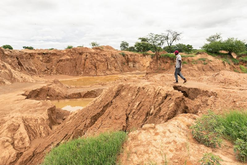 Heavy rains burst a dam wall and flooded disused gold mine shafts in Zimbabwe, where at least 60 illegal miners were feared dead (AFP Photo/Jekesai NJIKIZANA)