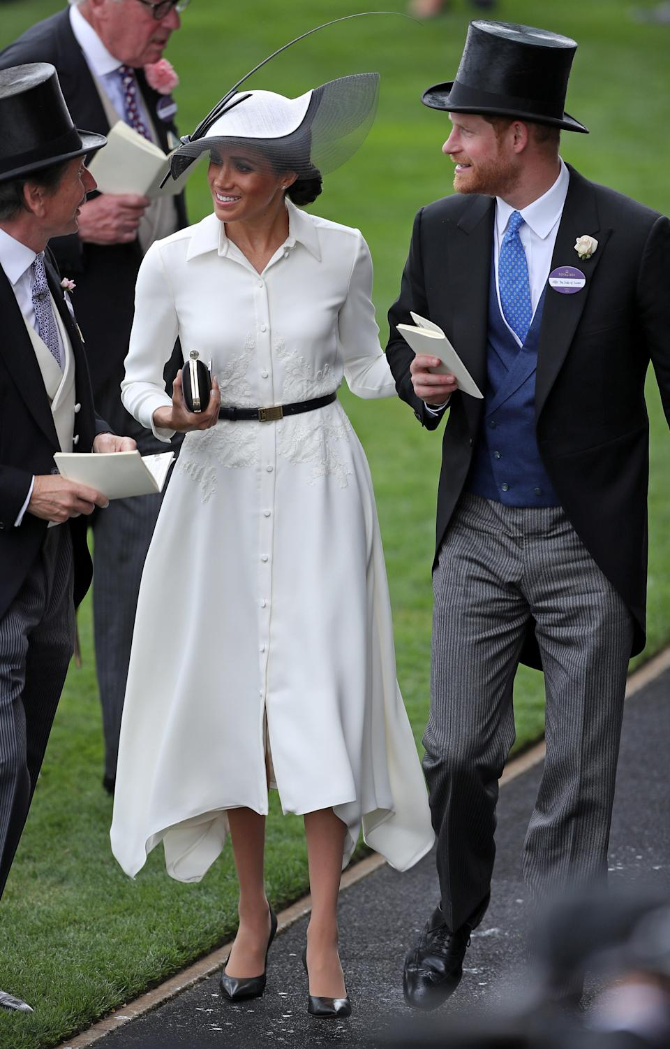 <p>The Duke and Duchess of Sussex finally made their Royal Ascot debut one month after the royal wedding on 19 June 2018. For the momentous occasion, Meghan wore her third Givenchy look accessorised with a monochrome hat by Philip Treacy. <em>[Photo: Getty]</em> </p>