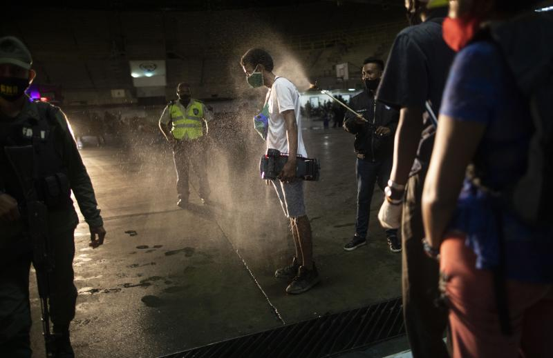 A man who was detained for not complying with COVID-19 regulations by breaking curfew and being out on the street drinking, is disinfected with an alcohol solution after he was transported to a coliseum in the Petare neighborhood of Caracas, Venezuela, early Saturday, Aug. 8, 2020, as part of an operation to educate residents on the risks of being out and socializing in groups amid the new coronavirus pandemic. Residents are released a few hours later after receiving instruction on best social distancing practices. (AP Photo/Ariana Cubillos)