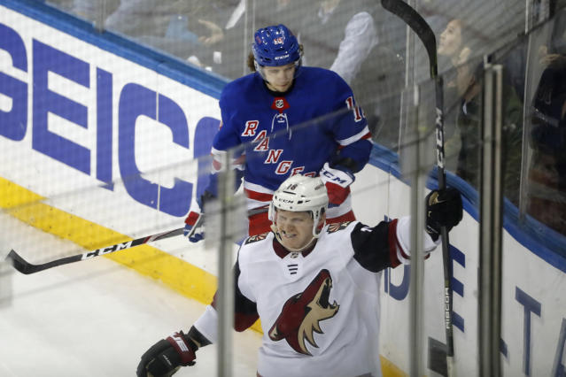Arizona Coyotes left wing Christian Dvorak (18) celebrates his overtime goal, as New York Rangers center Artemi Panarin (10) looks down, at the end of an NHL hockey game Tuesday, Oct. 22, 2019, in New York. The Coyotes won 3-2. (AP Photo/Kathy Willens)