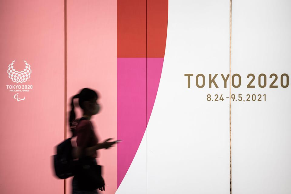 A woman wearing a face mask walks past a display promoting Tokyo 2020. The opening ceremony is scheduled for July 23.