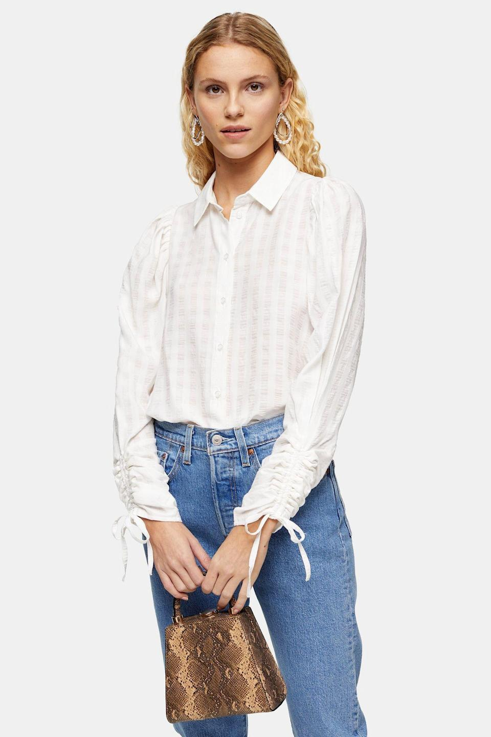 """<p><strong>Topshop</strong></p><p>topshop.com</p><p><strong>$37.50</strong></p><p><a href=""""https://go.redirectingat.com?id=74968X1596630&url=https%3A%2F%2Fus.topshop.com%2Fen%2Ftsus%2Fproduct%2Fwhite-drawstring-sleeve-shirt-9935732&sref=https%3A%2F%2Fwww.cosmopolitan.com%2Fstyle-beauty%2Ffashion%2Fg30933395%2Ffall-fashion-trends-2020%2F"""" rel=""""nofollow noopener"""" target=""""_blank"""" data-ylk=""""slk:Shop Now"""" class=""""link rapid-noclick-resp"""">Shop Now</a></p><p>A button-up blouse with the ruched detail will zhuzh up your office attire. </p>"""