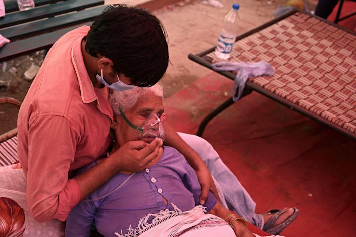 A family member comforts a woman breathing with the help of oxygen being provided by a Gurdwara, a place of worship for Sikhs, under a tent installed along the roadside as the COVID-19 pandemic hits Ghaziabad, India, May 4, 2021. / Credit: TAUSEEF MUSTAFA/AFP/Getty