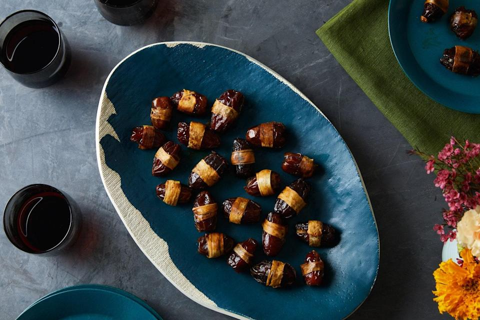 "Many of the best appetizer recipes can be reworked for folks who don't eat meat. This vegetarian version of the classic hors d'oeuvre uses soy sauce, smoked paprika, and smoked almonds to pack savory flavor into stuffed dates. <a href=""https://www.epicurious.com/recipes/food/views/parsnip-wrapped-devils-on-horseback?mbid=synd_yahoo_rss"" rel=""nofollow noopener"" target=""_blank"" data-ylk=""slk:See recipe."" class=""link rapid-noclick-resp"">See recipe.</a>"