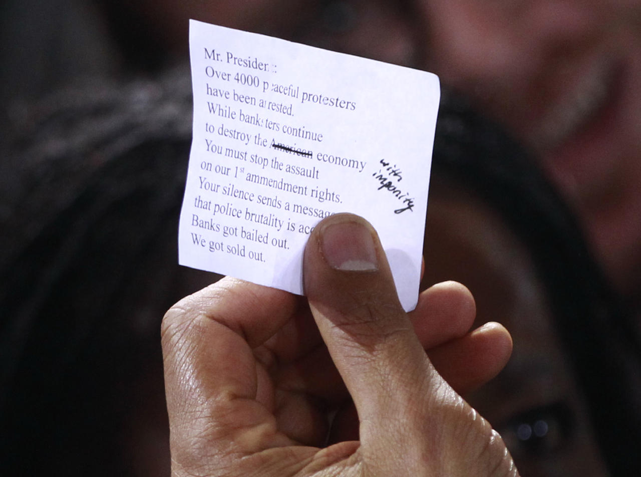President Barack Obama holds a note given to him by a protester as he greeted audience members after speaking about jobs, Tuesday, Nov. 22, 2011, at Manchester High School Central in Manchester, N.H. (AP Photo/Charles Dharapak)