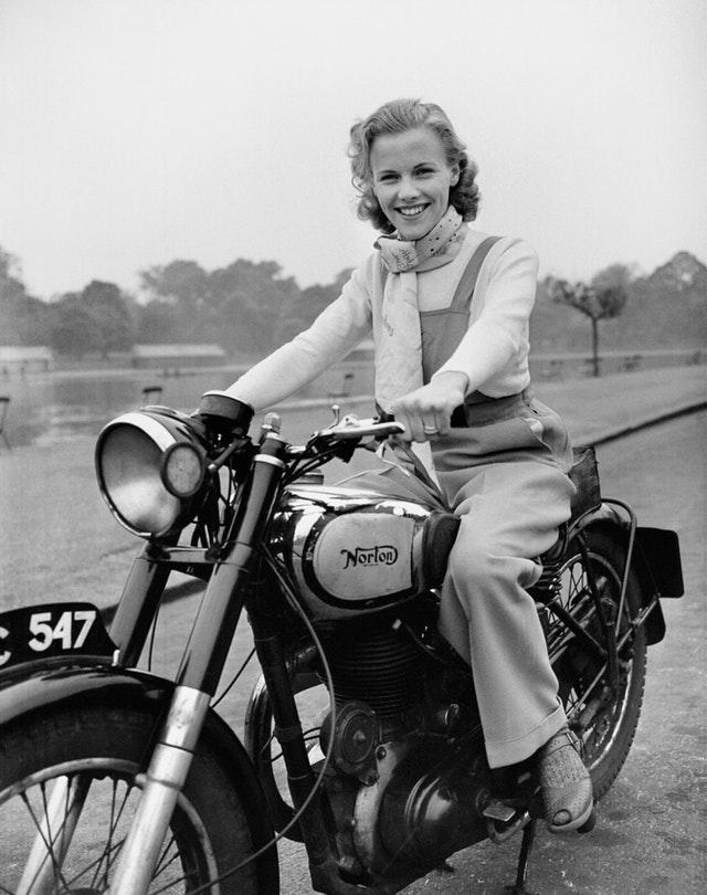 Honor Blackman pictured riding her Norton Big Four motorcycle through Hyde Park in London at age 23 in 1949 (PA)