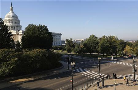 A few pedestrians wait to cross the street to the U.S. Capitol in Washington, October 2, 2013. REUTERS/Jonathan Ernst