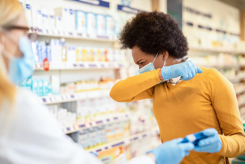 woman coughing while wearing a mask and asking for medication at a pharmacy