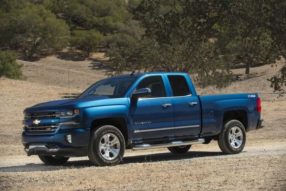 A blue 2017 Chevrolet Silverado pickup parked on a dirt road.