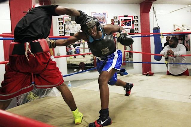 In this Sept. 18, 2012, photo, Olympic gold medal boxer Claressa Shields spars with training partner Ardreal Holmes at the Berston Field House in Flint, Mich. Unwilling to accept a life of poverty, crime or worse, Shields found her family, her passion and her way out through a small, dark basement gym. (AP Photo/Carlos Osorio)