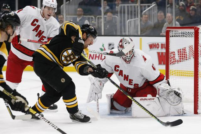 Boston Bruins' Brad Marchand tries to get a shot on Carolina Hurricanes' James Reimer during the second period of an NHL hockey game in Boston, Tuesday, Dec. 3, 2019. (AP Photo/Michael Dwyer)