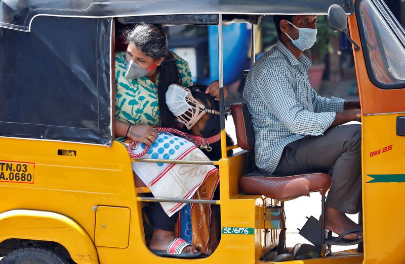 A dog wearing a protective mask is seen with its owner inside an autorickshaw during a 21-day nationwide lockdown to limit the spreading of coronavirus disease (COVID-19) in Chennai