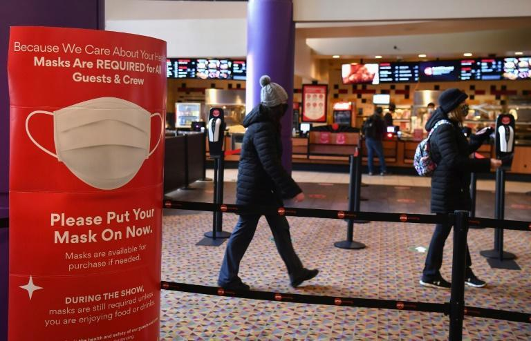 A mask requirement poster welcomes patrons at AMC Empire 25 off Times Square as New York City's cinemas reopened on March 5, 2021