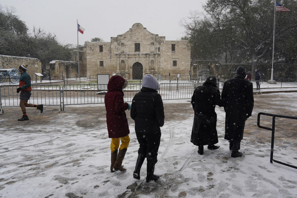 People walk through the snow as they pass the Alamo, Thursday, Feb. 18, 2021, in San Antonio. Snow, ice and sub-freezing weather continue to wreak havoc on the state's power grid and utilities. (AP Photo/Eric Gay)
