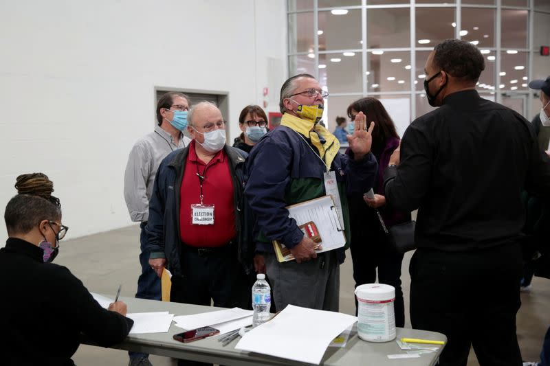 A poll challenger argues with police and officials after being asked to leave due to room capacity at the TCF Center after Election Day in Detroit, Michigan