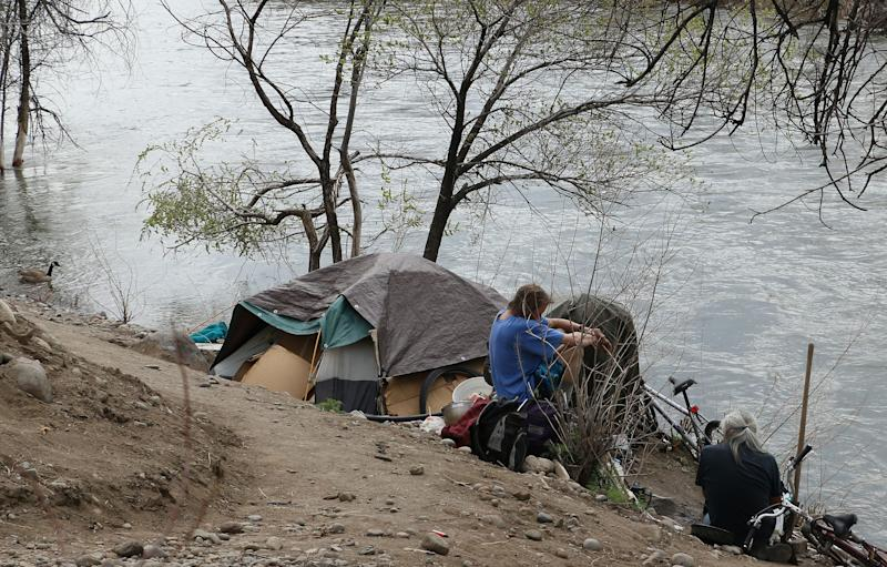 A camp for homeless people is seen along the edge of the Truckee River in Reno on April 5, 2018. The arrival of the Tesla Gigafactory has exacerbated a housing shortage in the Reno area.
