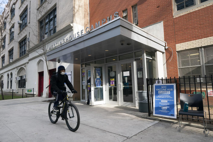 FILE - In this Jan. 21, 2021, file photo, a cyclist passes a closed vaccination center at the George Westinghouse High School in New York. An increasing number of COVID-19 vaccination sites around the U.S. are canceling appointments because of vaccine shortages in a rollout so rife with confusion and unexplained bottlenecks. (AP Photo/Mark Lennihan, File)